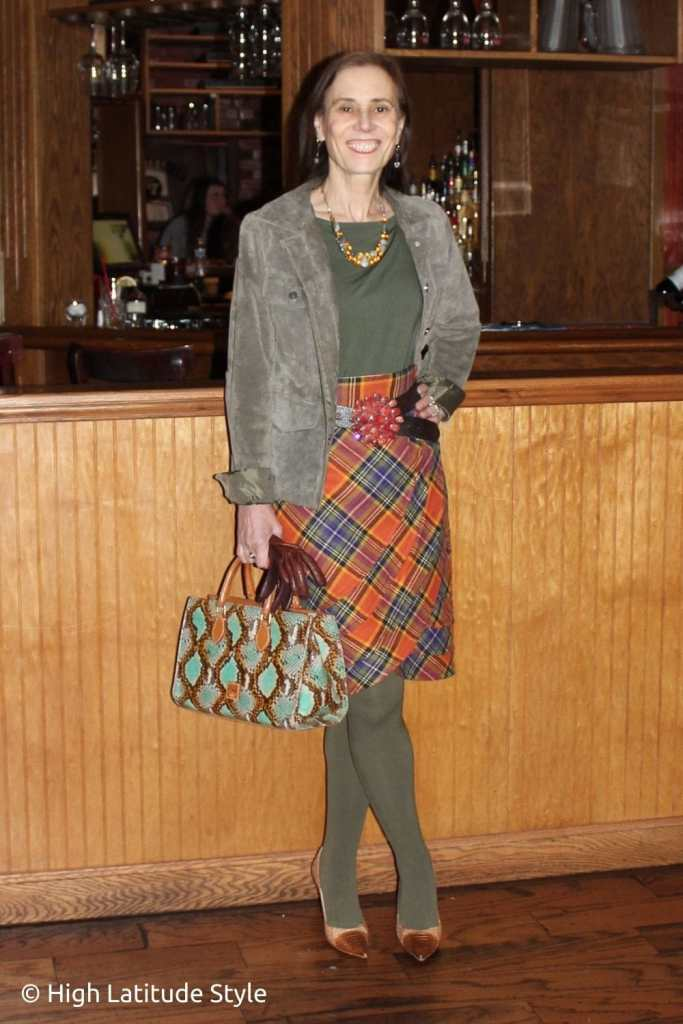 fashion blogger in plaid bottom, olive top and tights, suede jacket, snake print bag