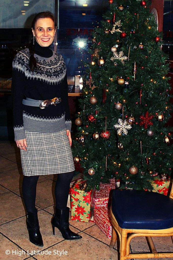 fashion blogger in hounds tooth skirt, tights, Fair Ilse sweater, customized jewelry in front of a Christmas tree
