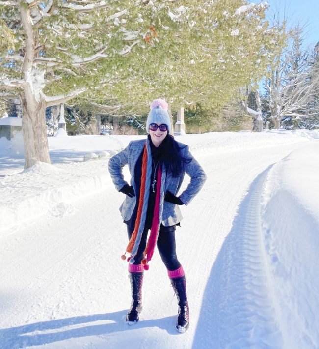 lifestyle blogger Shelbee in blazer, knit scarf, pom pom hat, pants, boots in snow landscape