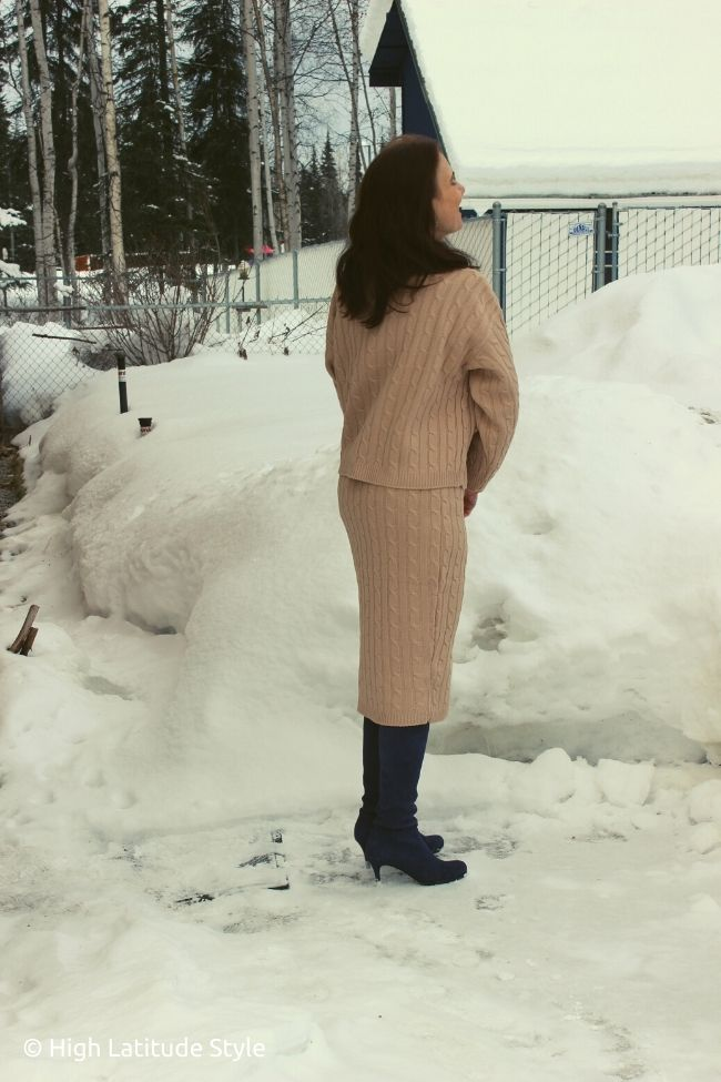 backview of woman with long brown hair in posh all spring neutrals knitwear, tall boots
