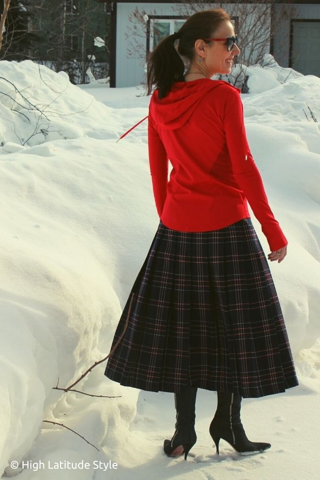 stylist wearing a fun hoodie with pleated tartan skirt and boots
