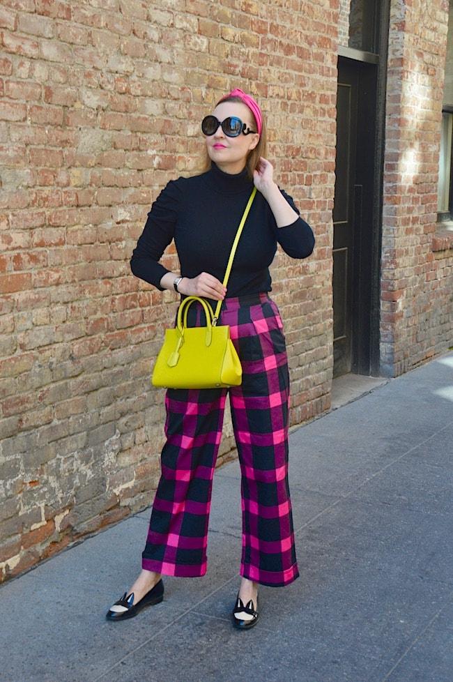 Katie in pink blue plaid pants, black top, yelow bag