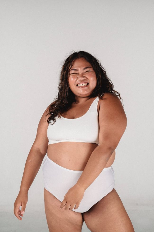 happy cheerful overweight asian woman dancing in bra and briefs