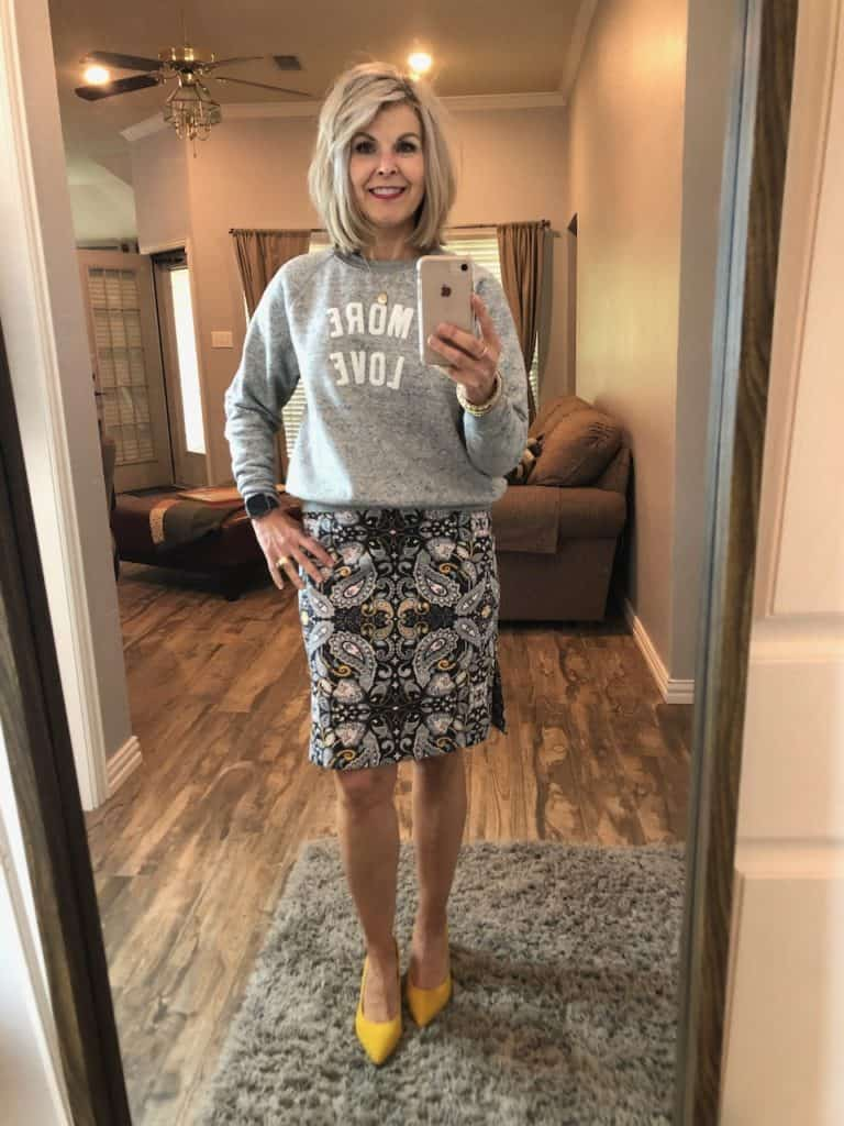Carrie in skirt and sweater top with yellow shoes
