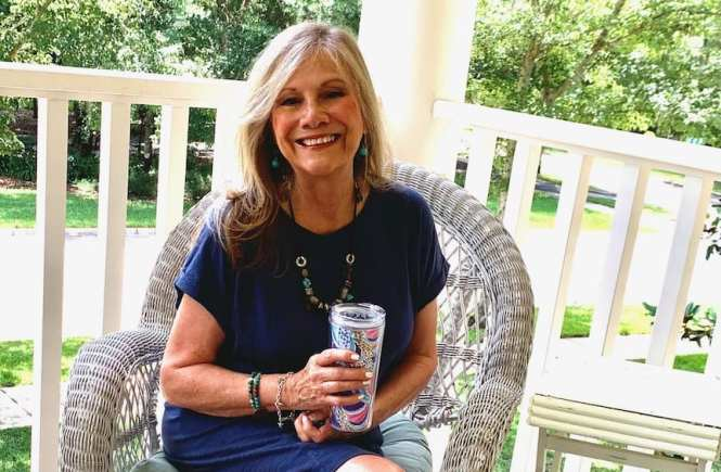 Rosemary of Distinctly Southern Style in blue denim dress sitting on a porch