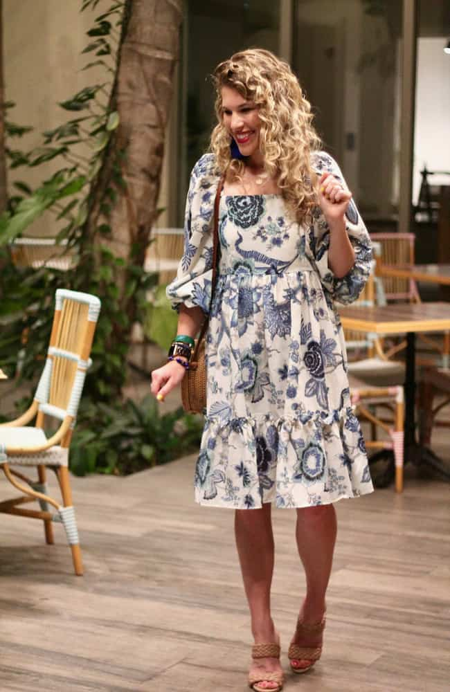 Laura in floral print dress with ruffles in the breakfast area of a hotel