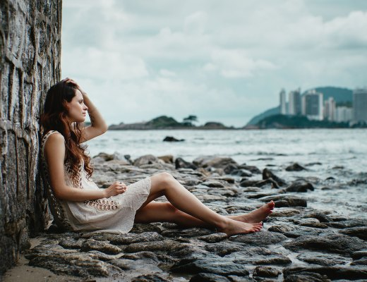 A highly sensitive woman sits by the ocean trying to deal with negative emotions.