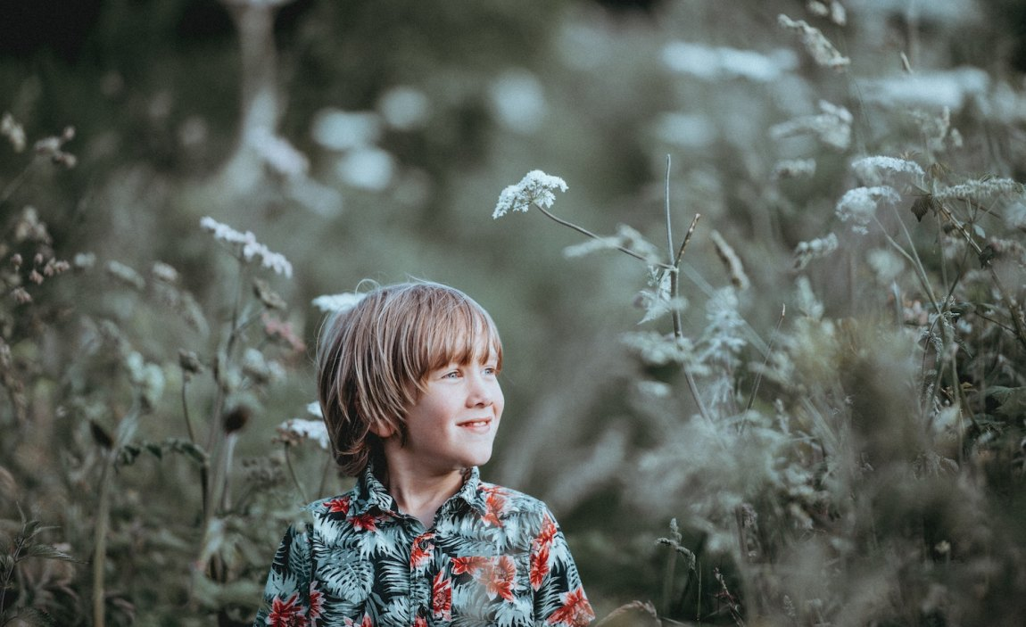 A highly sensitive child (male) in a field looking thoughtfully into the distance.
