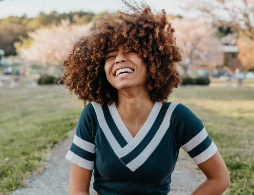 A highly sensitive person (woman) laughs with joy from a daily affirmation