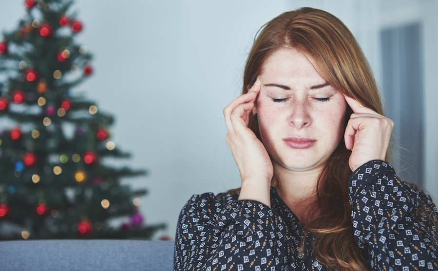 A highly sensitive person holding her hands to her head to deal with holiday stress in front of a Christmas tree