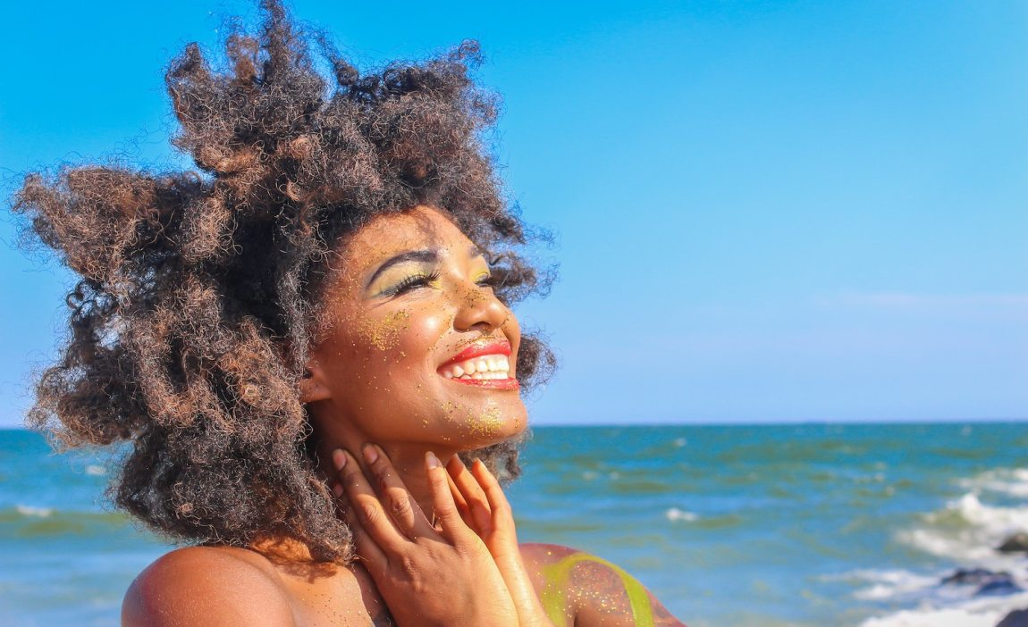 An empath (woman) smiling in the sunshine and living her best life.