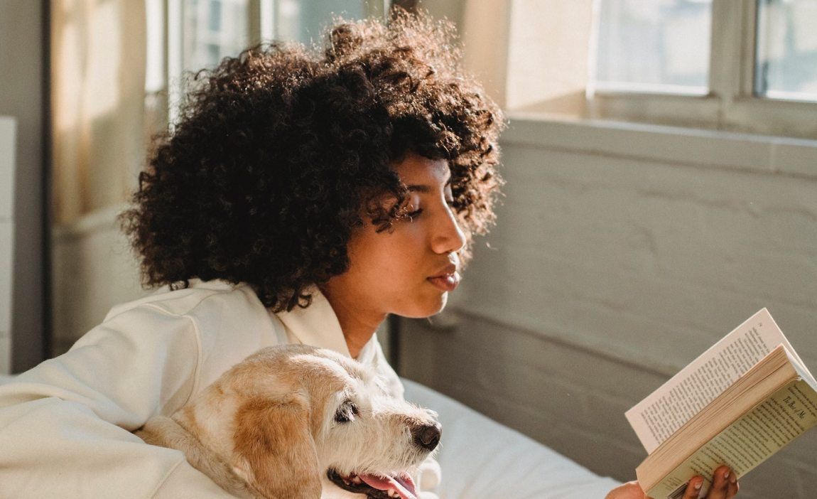 A woman spending a peaceful day at home with her dog, her book, and the sun shining on her cozy bed.