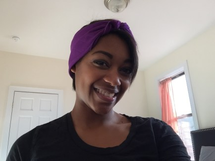 Square purple headscarf folded into rectangle and tied around head with ends tucked in.
