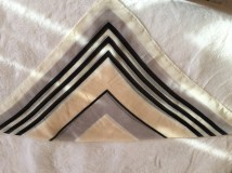Square, tan headscarf folded into triangle on white background.