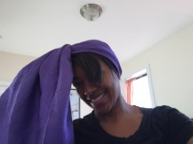 Long, rectangular, purple scarf tied around head with one piece wrapped around the other to create one loose end.