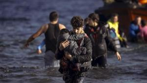 A young man carries a child as refugees and migrants arrive on a boat on the Greek island of Lesbos, November 7, 2015. REUTERS/Alkis Konstantinidis