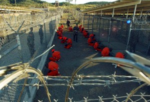 "Detainees in orange jumpsuits sit in a holding area under the watchful eyes of military police during in-processing to the temporary detention facility at Camp X-Ray of Naval Base Guantanamo Bay in this January 11, 2002 file photograph. A cache of classified U.S. military documents provides intelligence assessments on nearly all of the 779 people who been detained at the Guantanamo Bay prison in Cuba. The secret documents, made available to The New York Times and several other news organizations, reveal that most of the 172 remaining prisoners have been rated as a ""high risk"" of posing a threat to the United States and its allies if released without adequate rehabilitation and supervision, the newspaper said in its report late on April 24, 2011.  REUTERS/Stringer/Files (CUBA - Tags: CRIME LAW POLITICS) - RTXL0IH"
