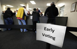 In this Sept. 29, 2016, photo, local residents receive their ballots at the Polk County Election Office on the first day of early voting in Des Moines, Iowa. Many Americans have at least some doubts about votes in this year's presidential election will be counted accurately, and a significant number are concerned about the possibility of interference in the election by foreign hackers. (AP Photo/Charlie Neibergall)