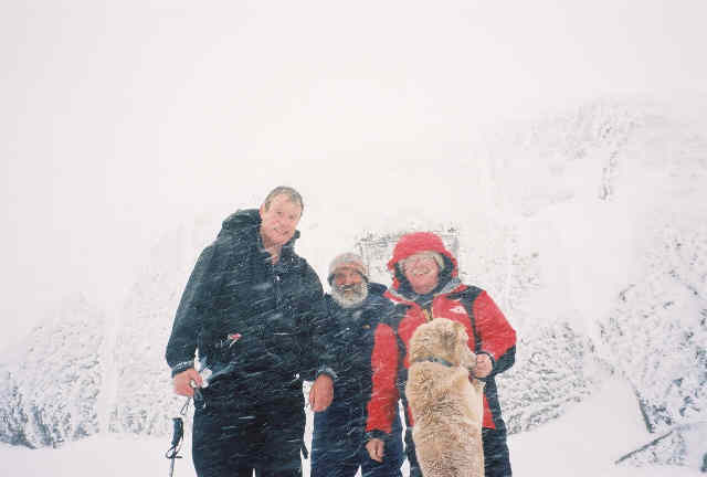 Roger Rowlett, Mario Locatelli, Stony Burke and Zephyr pose for photo just as a white out approaches on the Marcy summit (photo by Stony Burke).