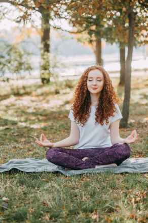Woman doing yoga on grass with trees in background