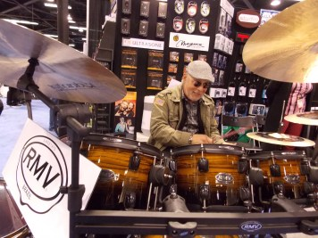 Man testing out drum kit at the RMV Drum booth at NAMM 2016