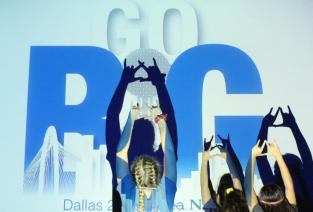 """Students lock their fingers and create silhouettes in front of a projection featured in the ballroom where the """"Country Meets City"""" dance took place. Students stood in front of the Reunion Tower (the """"i"""" in """"Go Big"""") and made silly shapes such as that of dogs. Photo by Rachel Bullock"""