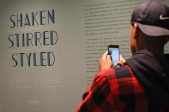 """""""Shaken, stirred, styled,"""" the wall reads, lightly illuminated for visitors such as senior Kevin Garcia. Garcia and the DPMHS Media team walked around various time periods of art in exhibits such as this, intently investigating the social and historical significance of different times and places of art. Photo by Rachel Bullock"""