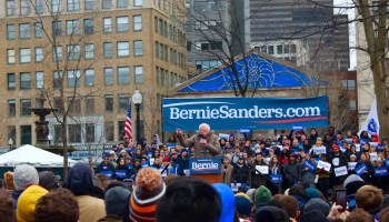 """Sanders' supporters wave blue """"Bernie"""" signs and chant the campaign's slogan: """"Not me, Us."""""""
