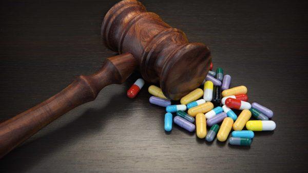 Judges Gavel And Medication On Black Wood Grunge Background pills big pharma lawsuit