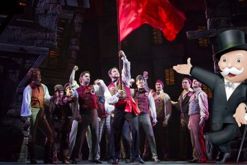 mister monopoly gestures at the revolutionaries in les miserables