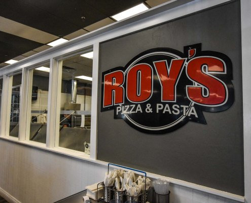 the logo of Roy's Pizza Restaurant inside the store interior