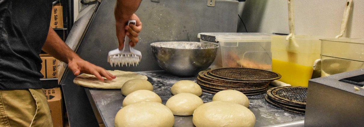 chef making pizza dough inside Roy's Pizza restaurant kitchen