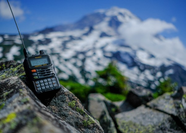 Yaesu VX-6R with Elastic Signal Stick on a rocky peak with a blurry Mount Rainier in the background