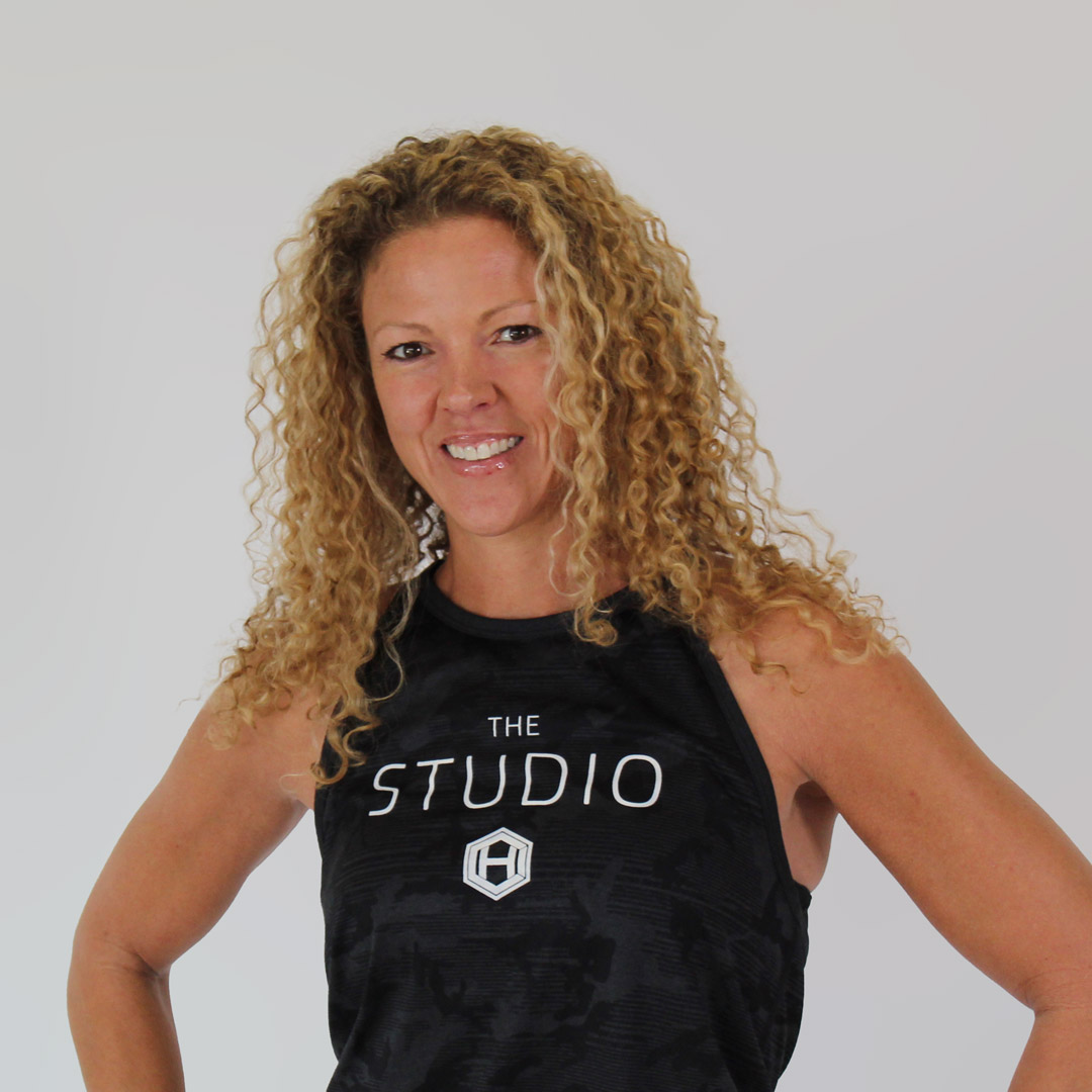 Woman with brown eyes and blonde curly hair smiling with her hands on her hips