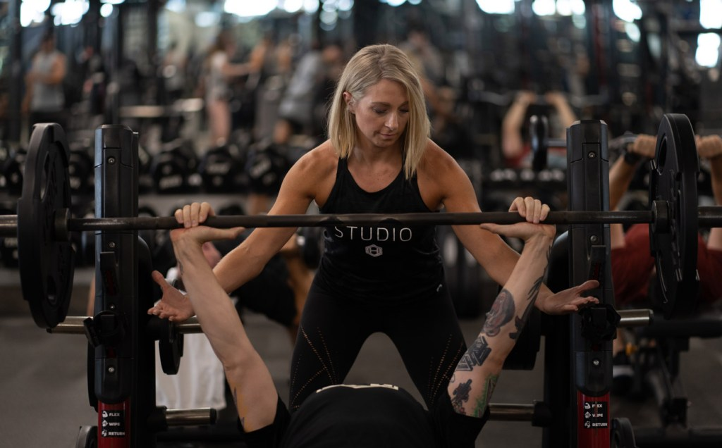 Woman spotting a man bench pressing in a weight room