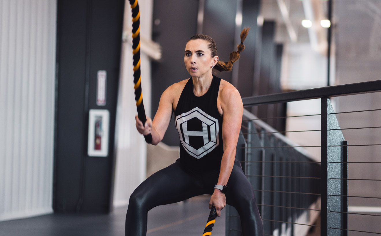 Athletic woman using battle ropes to work out