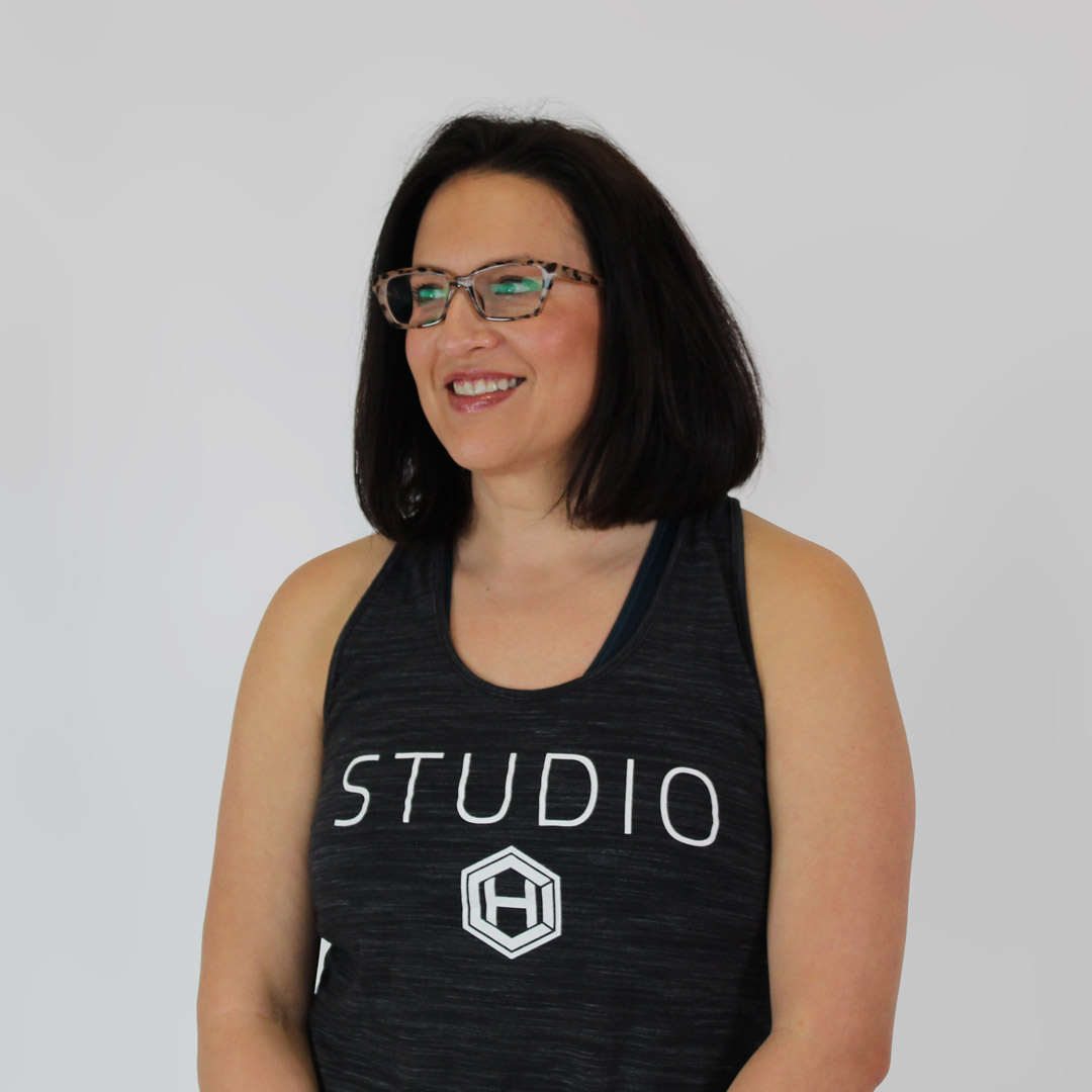 Woman with black hair and glasses wearing a black HCI studio tank top, smiling and looking to the left