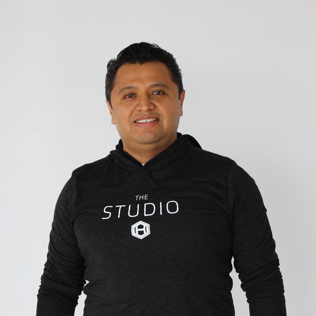 Latino man smiling and wearing a black, HCI studio hoodie