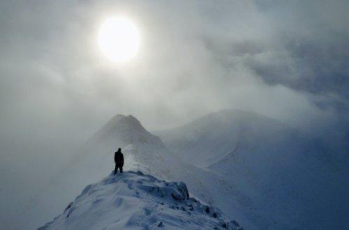 Winter walk on a snowy ridge in Scotland