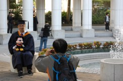 Graduate with stuffed Mickey Mouse