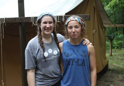 Young women standing outside a tent