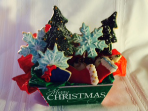 Five Large Christmas cookies on sticks in a basket with smaller cookies inside