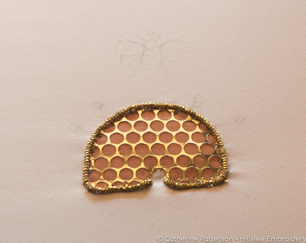 a hand embroidered bee hive stitched using sequin waste