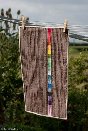 Back of quilt; rainbow strip on neutral background