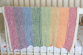 handmade knitted cotton baby blanket in rainbow stripes hanging over cot