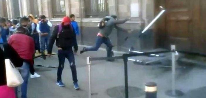 Normalistas vandalizan una puerta de Palacio Nacional