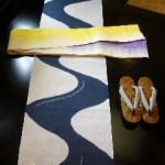 麻の浴衣に麻の半巾帯。大きな水流を絞りで染分けた個性的な一枚です。黄色と紫に染分けた帯と合わせて大胆に着こなして下さい。
