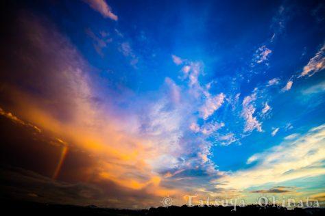 東の空に虹、上空は晴れ、西は夕焼け