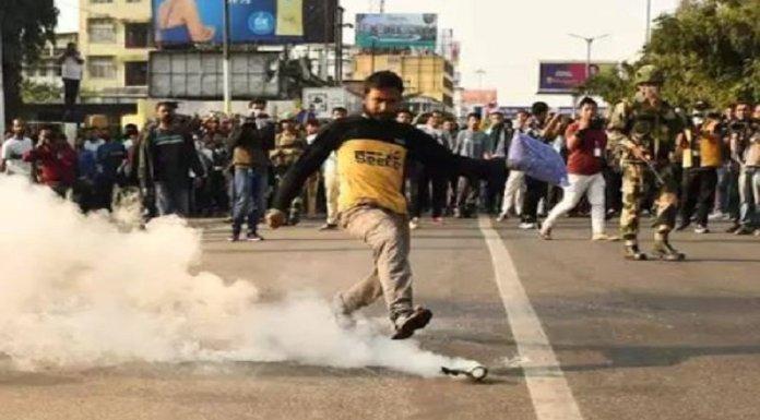 नागरिकता विधेयक के खिलाफ हिंसा के दौरान आँसू गैस के गोले को लात मारता प्रदर्शनकारी (TOI से साभार)