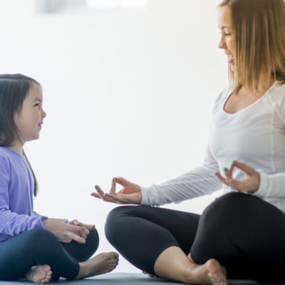 A single mother and her elementary age daughter are meditating together at home.